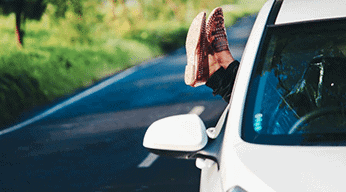 womens feet wearing blue jeans and red and white shoes sticking out of white car driving on road with green trees