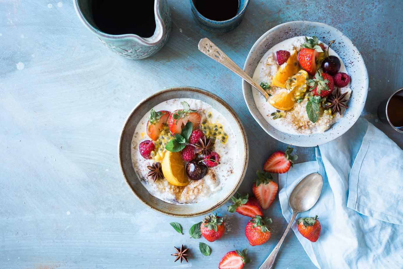 two big bowls of steel cut oats topped with berries, sliced oranges and grapefruit, grapes and soaking in milk
